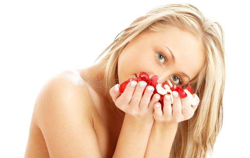 Rubio encantador en balneario con los pétalos color de rosa rojos y blancos #2 foto de archivo