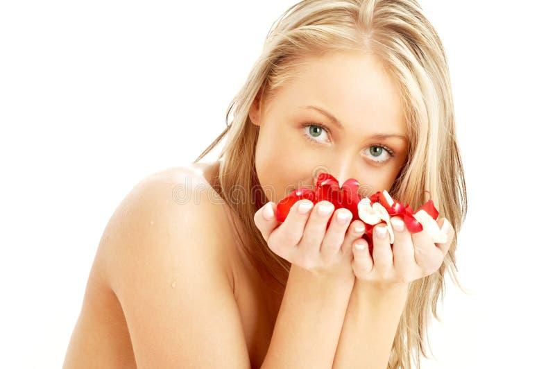 Rubio encantador en balneario con los pétalos color de rosa rojos y blancos fotos de archivo libres de regalías
