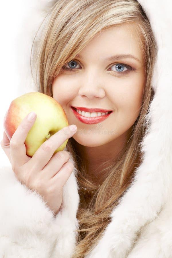 Rubio encantador en piel con la manzana imagen de archivo libre de regalías
