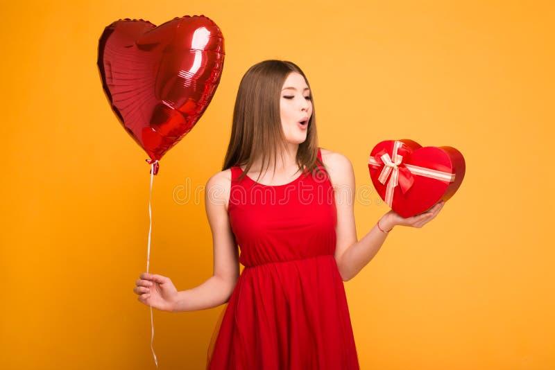 Rubio feliz en el vestido rojo que sostiene un globo y una caja de regalo imágenes de archivo libres de regalías