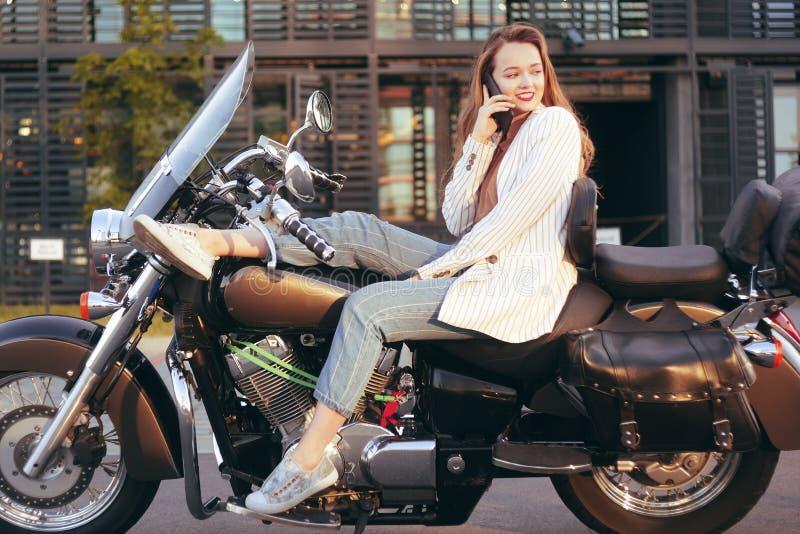 Rubio hermoso se sienta en una motocicleta cerca de la oficina La muchacha vino trabajar en una motocicleta La muchacha está habl foto de archivo libre de regalías