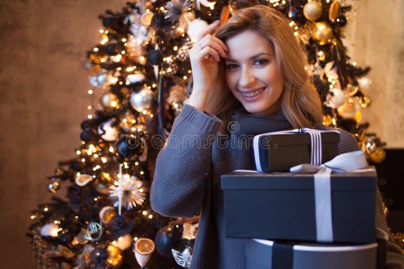 Rubio joven hermoso con las cajas de regalo debajo del árbol de navidad fotos de archivo libres de regalías