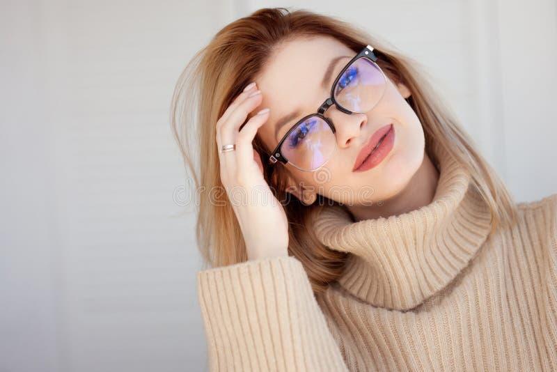 Rubio lindo joven con lentes y un suéter beige Mujer joven de moda elegante imagen de archivo libre de regalías