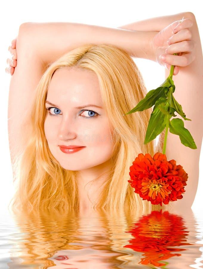 Rubio precioso con la flor en agua imagenes de archivo