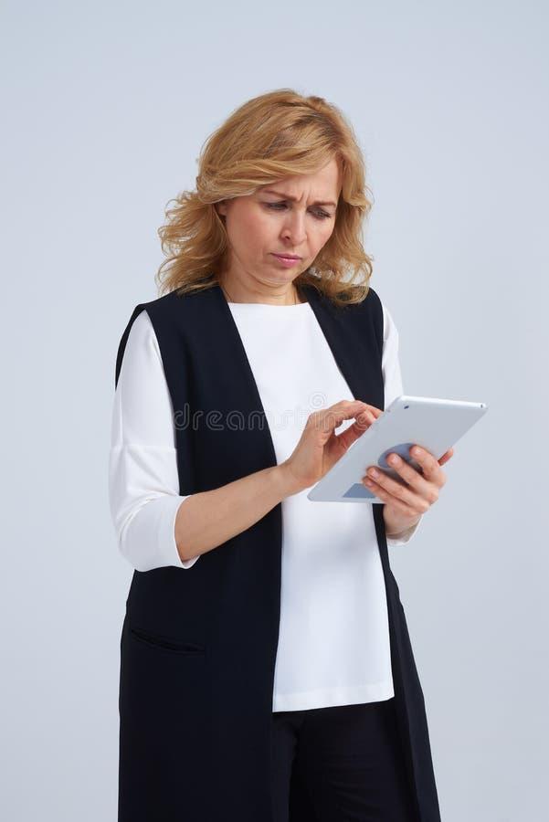 Rubio serio usando la tableta digital imagen de archivo libre de regalías