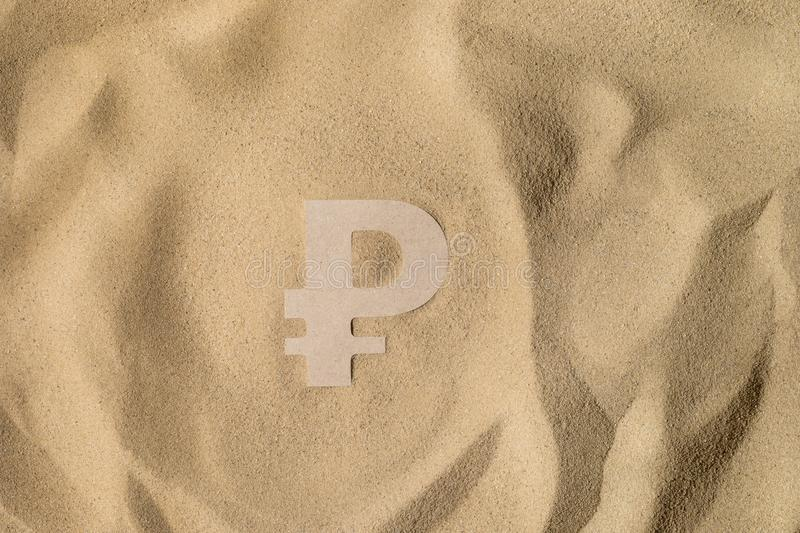 Ruble Sign On the Sand. Russian Ruble Symbol lies on the Sand in Direct Sunlight stock image