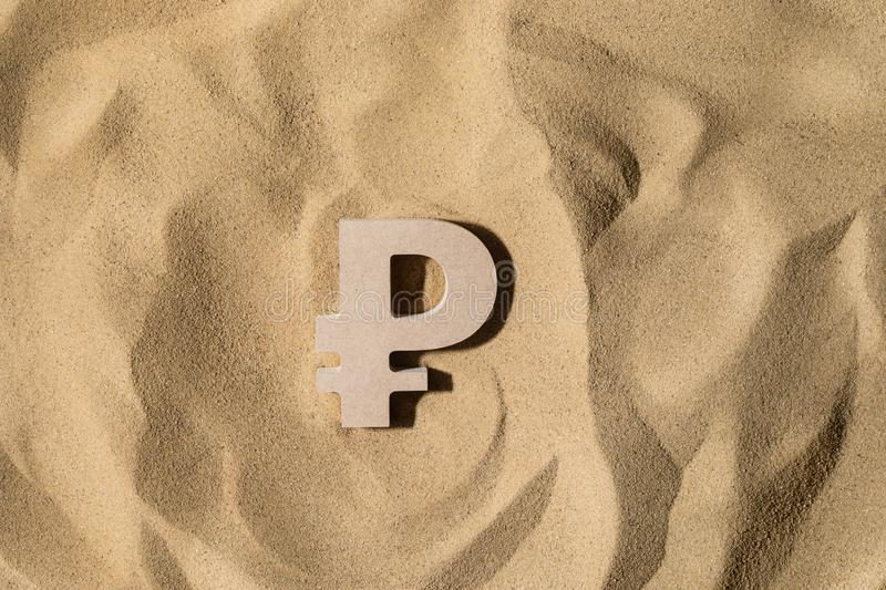 Ruble Sign On the Sand. Russian Ruble Symbol lies on the Sand in Direct Sunlight stock images
