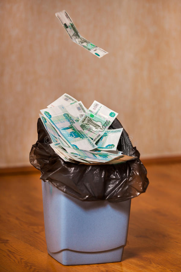 Rubles are thrown in the trash bin. One russian banknote flies in trash bin filled with russian money royalty free stock photo