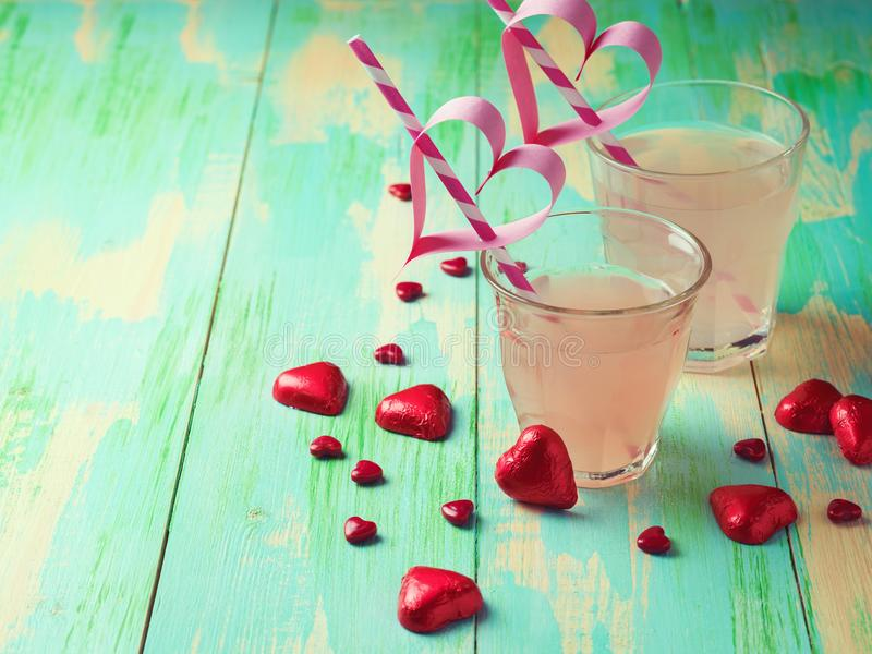 Ruby red grapefruit juice and heart shape chocolates. Over wooden background. Valentines day concept stock photos