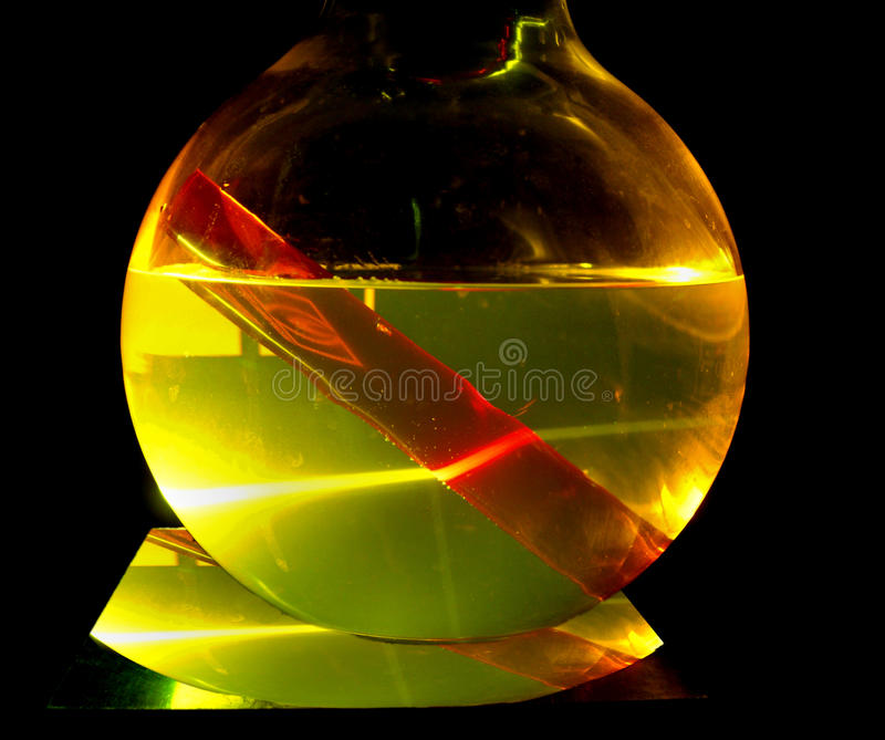Ruby rod in a dye solution under laser beam stock photography