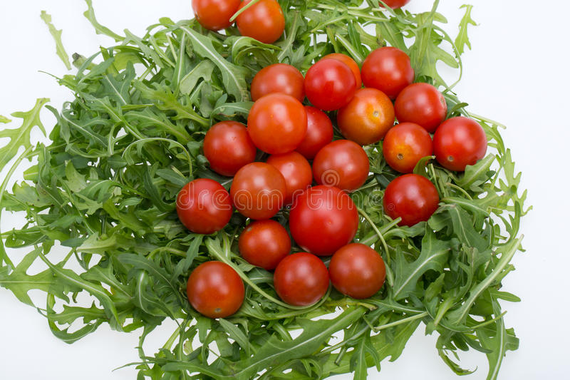Ruccola leaves and cherry tomatoes. Heap of ruccola leaves and cherry tomatoes stock images