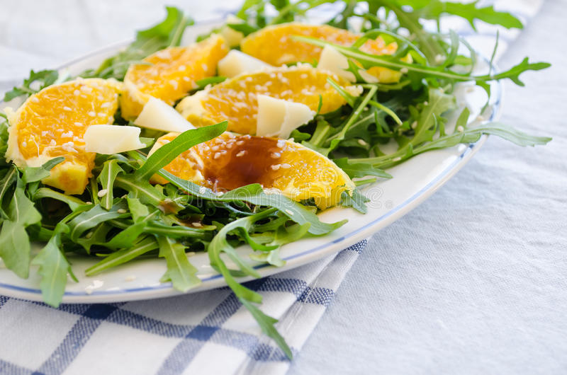Ruccola salad with orange, cheese, sesame and balsamic. On a blue fon royalty free stock photography
