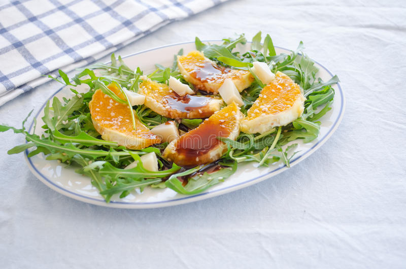 Ruccola salad with orange, cheese, sesame and balsamic royalty free stock photography