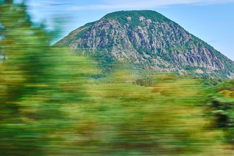 Ruch plamy wizerunku folliage gdy jadący szybko na drodze Przeciw górom na jasnym słonecznym dniu zdjęcie royalty free