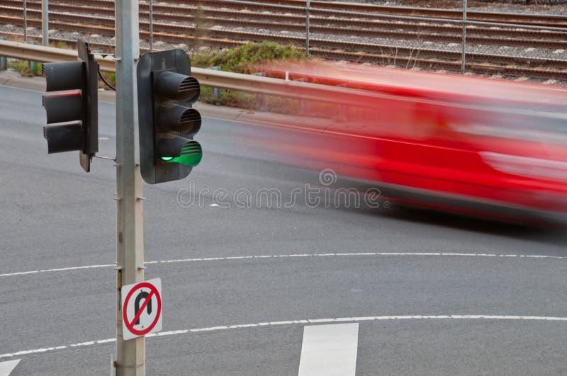 Ruch zamazany czerwony samochód z zielonym oświetleniem obraz royalty free