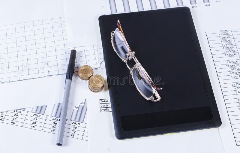 Ruchkaa preto e vidros da tabuleta que encontram-se nos quadros financeiros e nos gráficos fotografia de stock