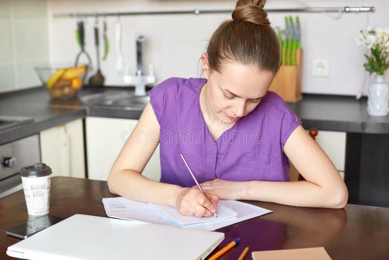 Ruchliwie kobieta pracuje od domu, pisze puszkowi coś w ślimakowatym notepad, siedzi przy kuchennym stołem, otaczającym z takeawa obrazy stock