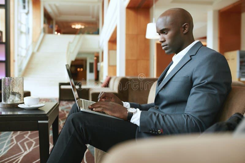 Ruchliwie młody biznesmen pracuje na laptopie w lobby fotografia stock