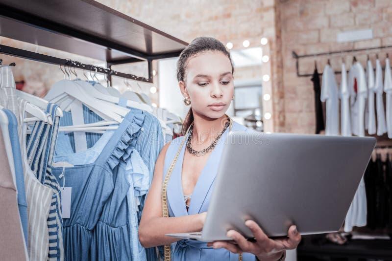 Ruchliwie pracowity projektant trzyma jej srebnego laptop podczas gdy rozkazywać tkaninę zdjęcia royalty free