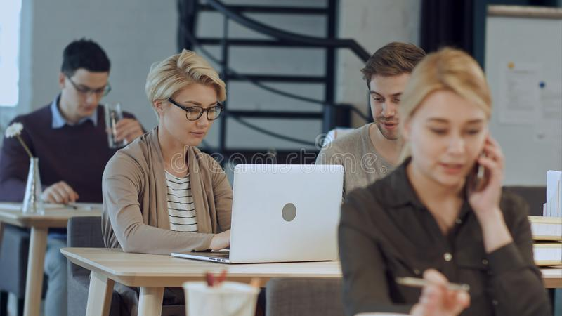 Ruchliwie projekta biuro z pracownikami przy biurkami zdjęcie stock