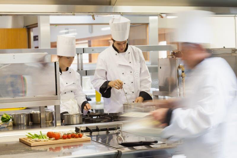 Ruchliwie szefowie kuchni przy pracą w kuchni obraz royalty free