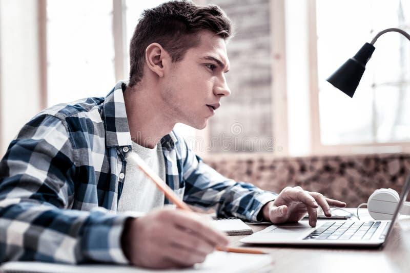 Ruchliwie uczeń marszczy brwi ekran i patrzeje podczas gdy robić notatce obrazy stock
