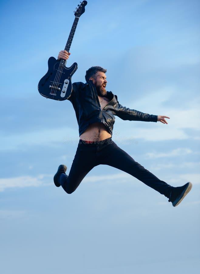 Ruchu i zabawy pojęcie Szczęśliwy młodego człowieka doskakiwanie w lotniczej, bawić się gitarze nad tłem i zdjęcia stock