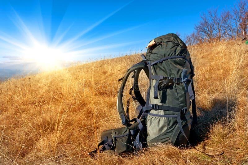 Rucksack auf Bergwiese stockbilder