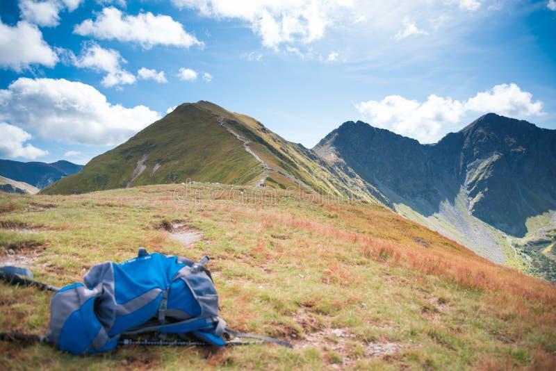 Rucksack blu e sentiero di montagna: attrezzature per trekking in background, attrezzi per camminare sulle montagne immagine stock