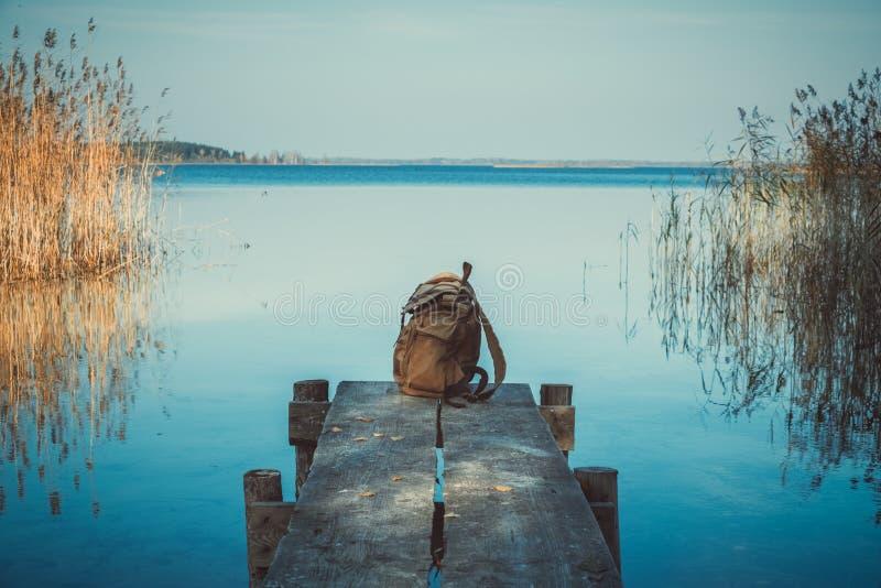 Rucksack des Reisenden auf der Holzpiste am blauen Sommersee stockbild