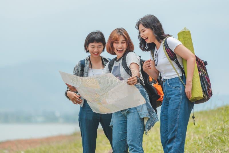 Rucksack-Holdingkarte mit drei Mädchen tragende stockbilder