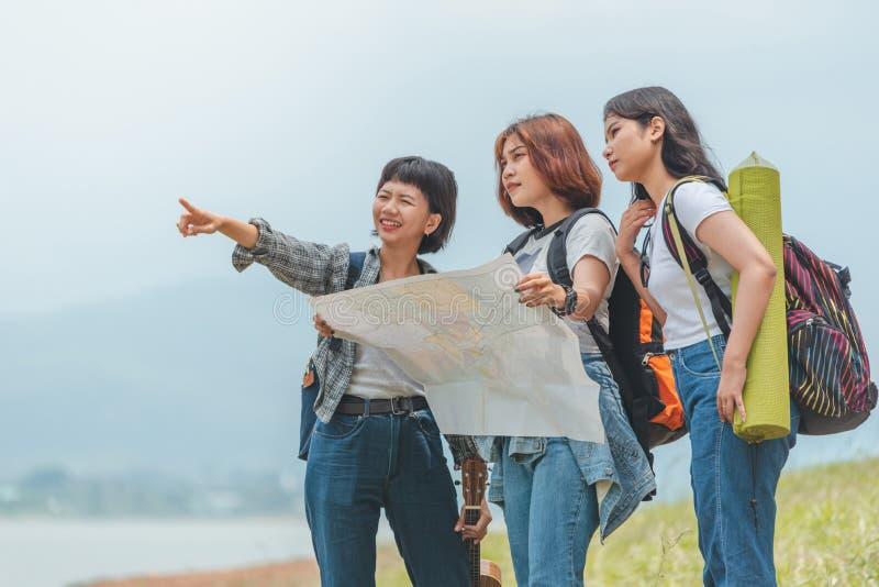Rucksack-Holdingkarte mit drei Mädchen tragende stockfotografie