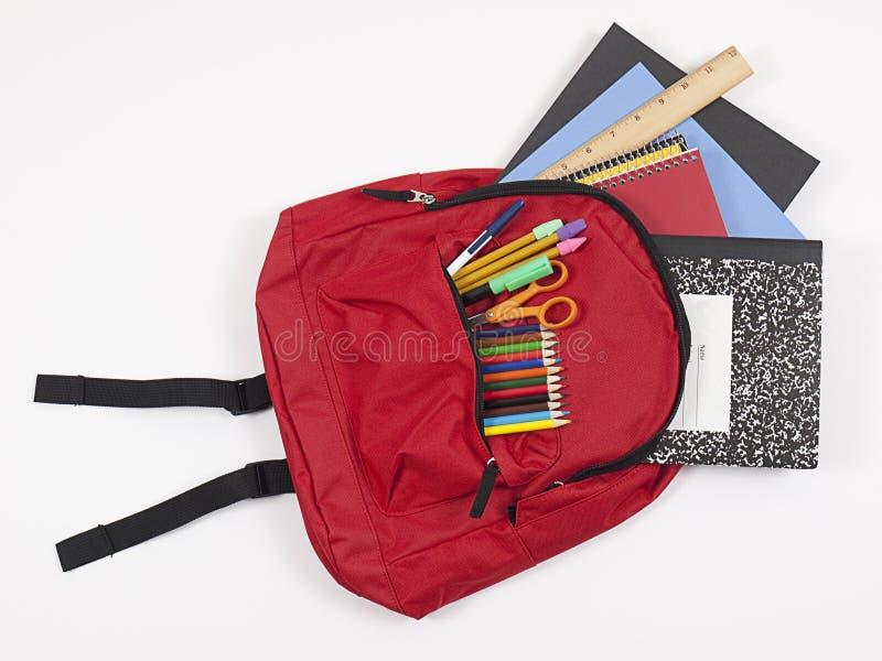 Rucksack mit dem Schulezubehör, das heraus verschüttet wird stockbild