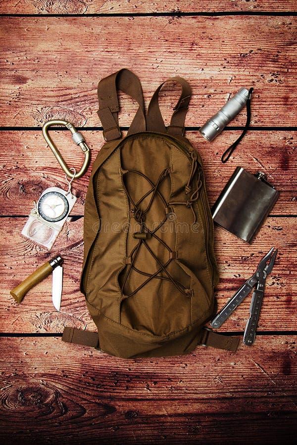 Rucksack und Gang für die Reise, die auf hölzernem Hintergrund kampiert stockbilder