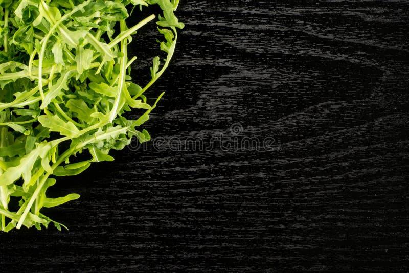 Rucola cruda fresca Rucola su legno nero immagine stock libera da diritti