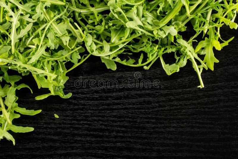 Rucola cruda fresca Rucola su legno nero immagini stock libere da diritti