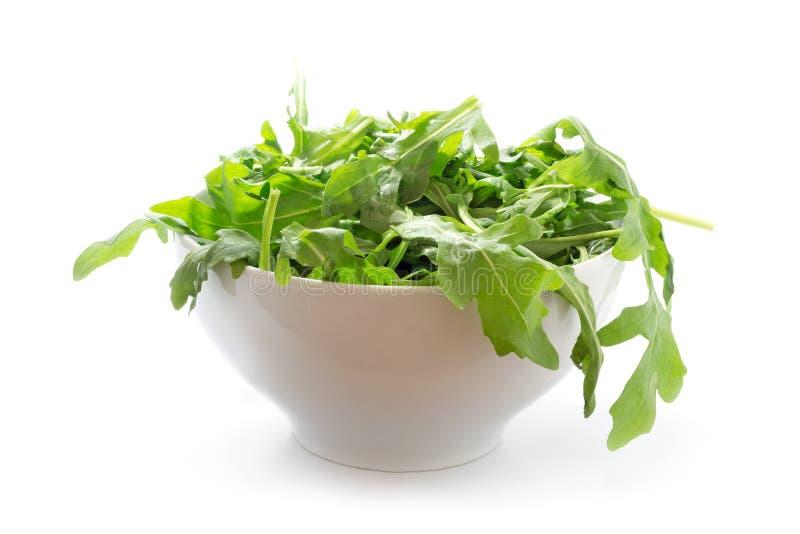 Rucola o el arugula, ensalada de cohete verde fresca en un cuenco blanco, es imagenes de archivo