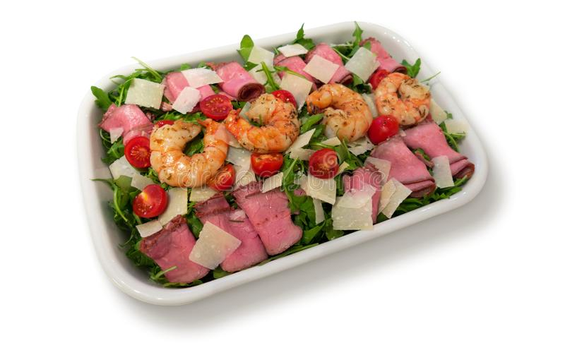 Rucola salad with roast beef; black tiger prawns; cherry tomatoes and parmesan cheese royalty free stock photos