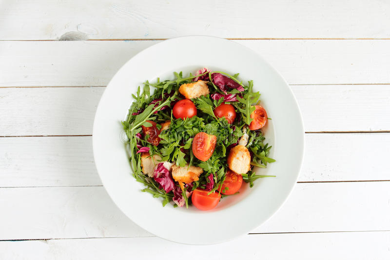 Rucola salad, tomatos and chicken on white plate royalty free stock images