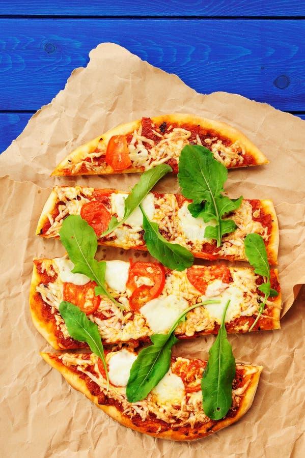 Rucolapizza op gerimpeld ambachtdocument met blauwe achtergrond stock foto