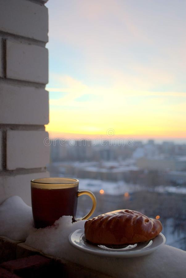 Ruddy pie and a mug of hot tea on a blurred background of sunset. Cold, weather, evening, hot, tea, mug, pie, russia, saucer, sunset, togliatti, tolyatti royalty free stock photography