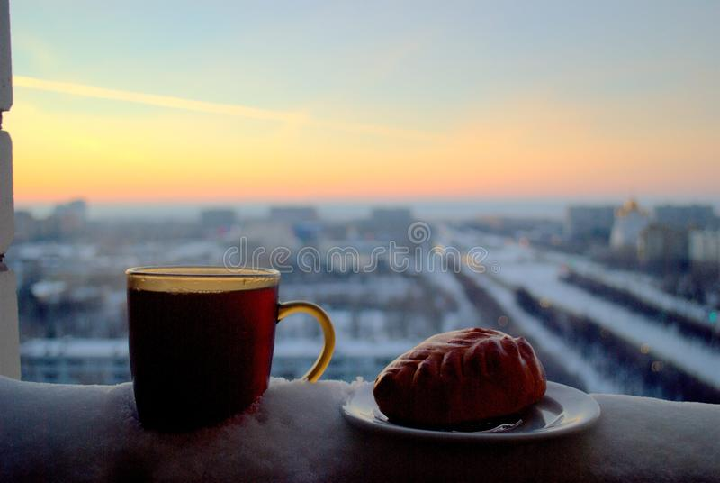 Ruddy pie and a mug of hot tea on a blurred background of sunset. Cold, weather, evening, hot, tea, mug, pie, russia, saucer, sunset, togliatti, tolyatti royalty free stock image