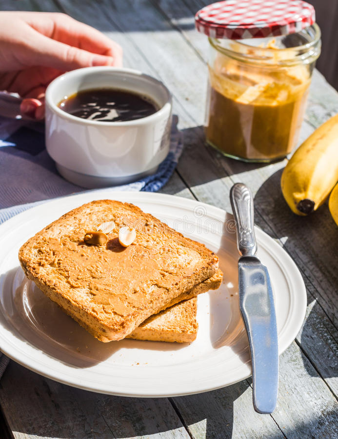 Ruddy toast with peanut butter, fresh bananas, coffee, breakfast royalty free stock photo