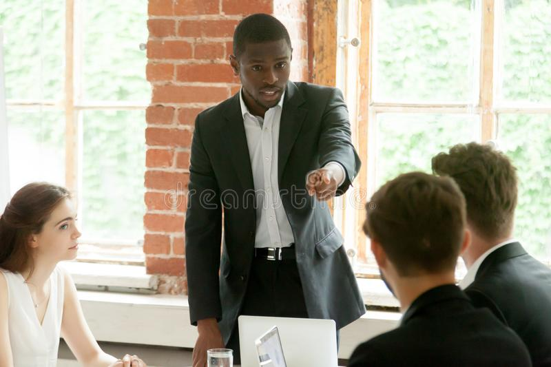 Rude african businessman pointing finger at white colleague duri stock photos