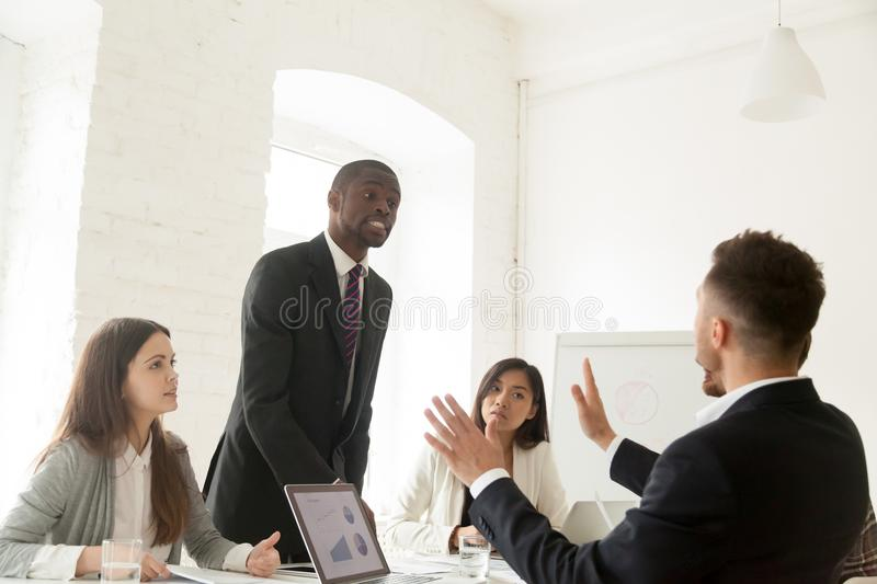 Rude angry african businessman arguing shouting at colleague dur. Rude angry african businessman arguing shouting at colleague at team meeting, mad black royalty free stock images