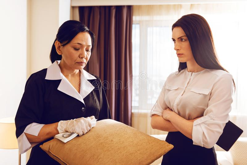 Rude brunette crossing arms on chest while listening her maid stock photography