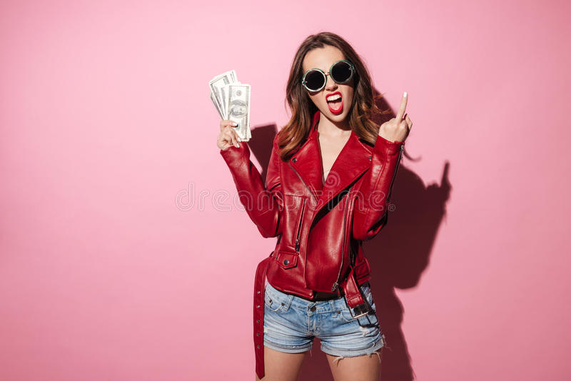 Rude crazy girl in leather jacket holding money banknotes royalty free stock photography