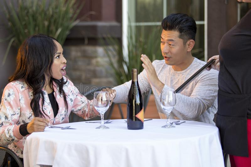 Embarrassed Boyfriend with Angry Girlfriend. Rude girlfriend complaining to a waitress in a restaurant with an embarrassed boyfriend trying to calm her down. The stock image