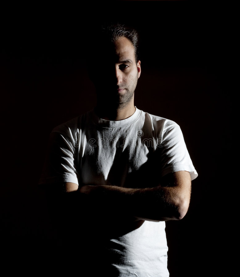 Rude mistery man. Dark image of a no shaved dangerous looking guy in a rude pose stock photos