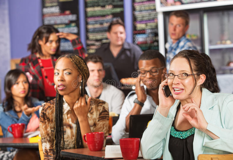 Rude Woman on Phone in Cafe. Annoyed students watching loud women on cell phone stock photography